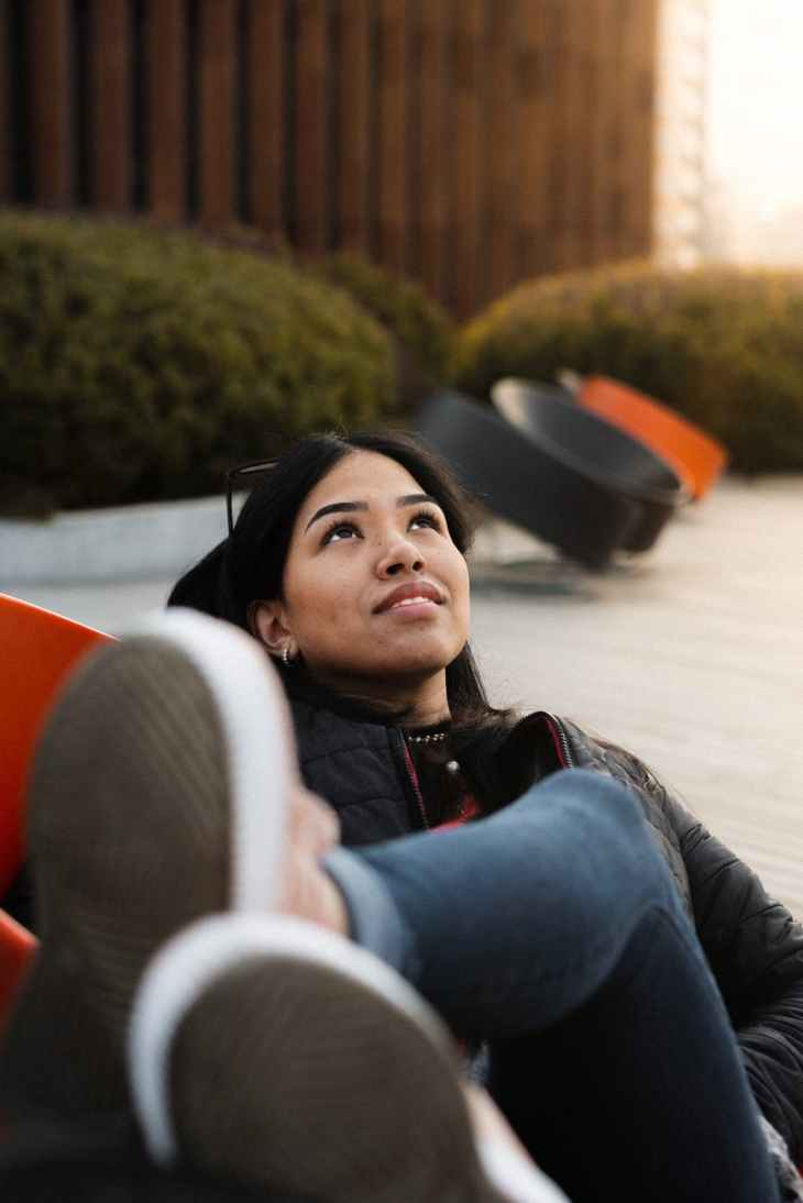 photo of woman in black jacket and blue denim jeans lying on chair while looking up