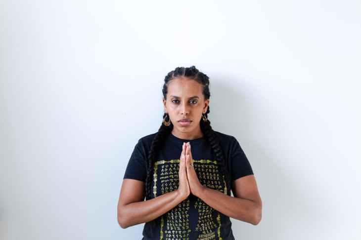 woman wearing black and yellow crew neck t shirt praying