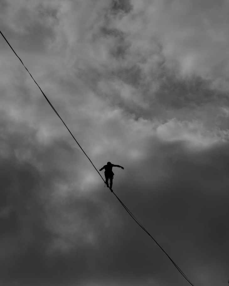 low angle photo grayscale of person tightrope walking